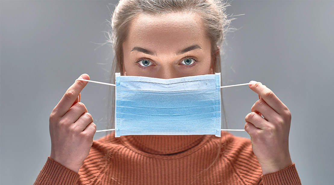 White female putting a surgical face mask