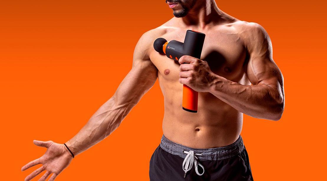 Fit lean muscular man using a jawku gun massager on his shoulder