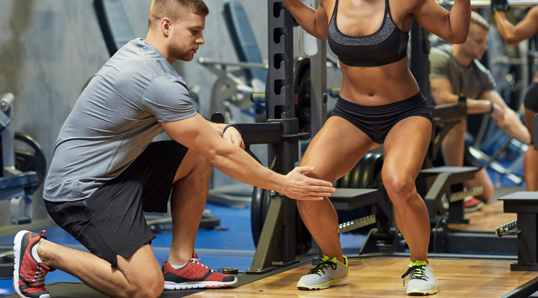 Male personal trainer training a fit female to properly do a barbell squat