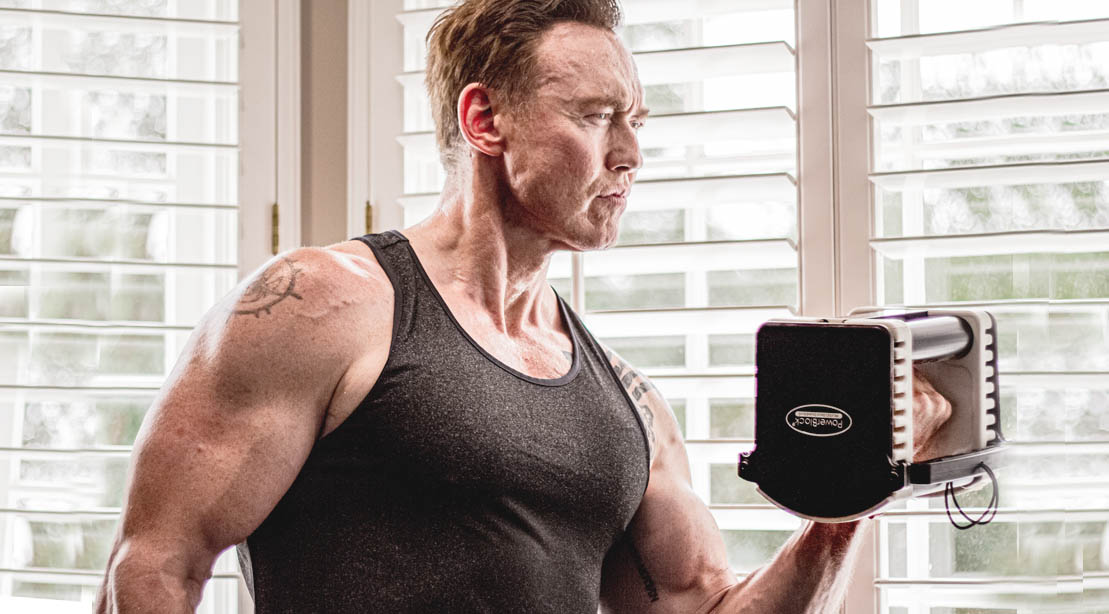 Actor Kevin Durand doing a bicep curl with a bowflex dumbbell