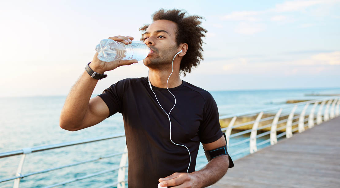 Black runner drinking a bottle of water as a good running tip and avoid dehydration
