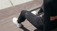 Female working out with a resistance band doing a seated clam shell exercise