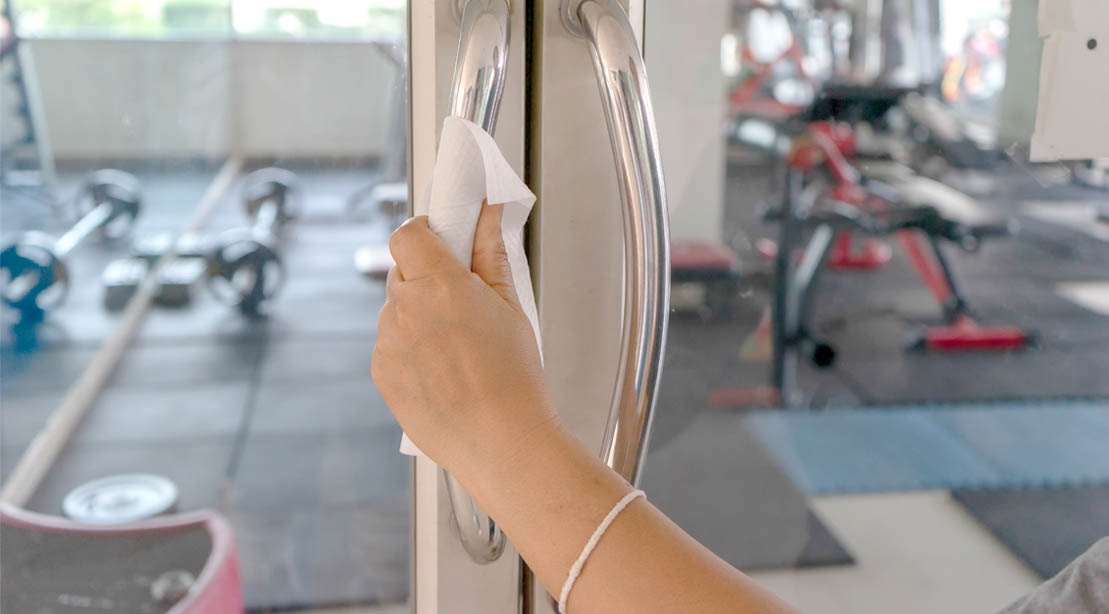 Female wiping down the handle of a glass door that leads to an empty gym