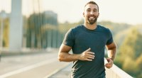 Fit happy man running outdoors and smiling