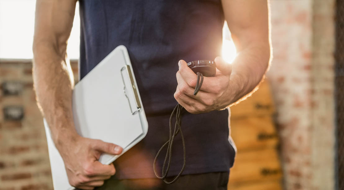 Fitness coach holding a stop watch and clip board to measure fitness goals and build muscle