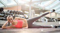 Happy-and-Healthy-Female-Fitness-Model-Working-Out-Her-Legs-In-A-Gym-With-Side-Lying-Leg-Lifts