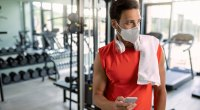 Physically fit gym goer wearing a mask in a gym