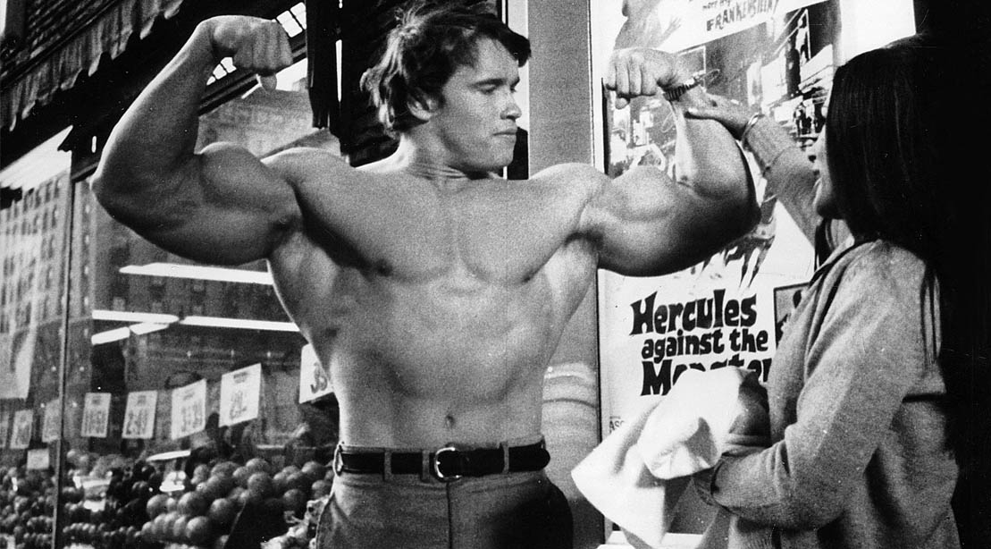 Young Arnold Schwarzenegger flexing his biceps