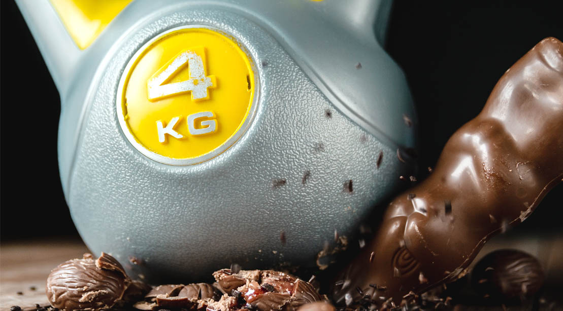 A 4 kilogram kettlebell weight cruching a chocolate candy bar and easter candies
