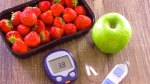 An apple and ripe strawberries and a glucometer used to monitor blood sugar