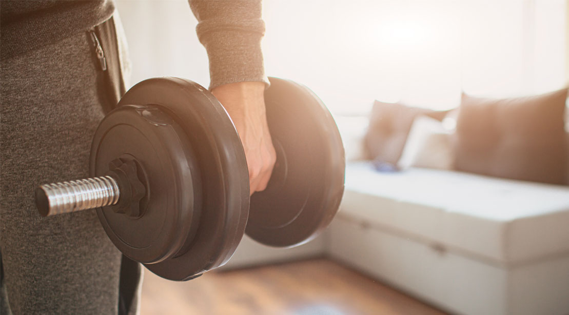 Beginner trainer working out with a dumbbell at home