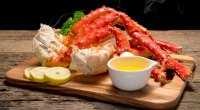 Alaskan king crab legs on a wooden serving board containing the micronutrient zinc