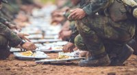 Navy Seal training during hell week while eating a meal on the ground