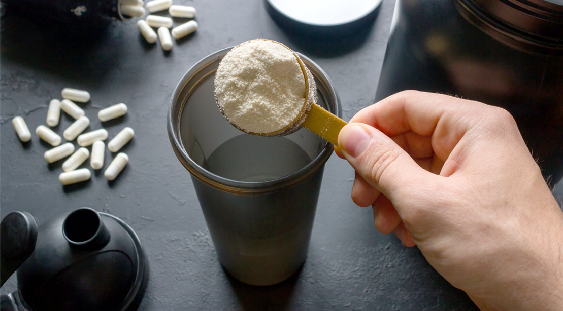 Protein powder and BCAAs powder in a scooper being poured into a protein shaker bottle