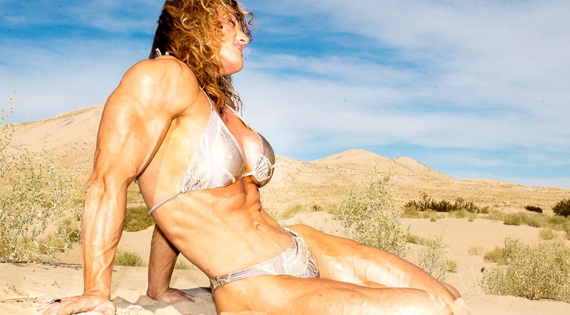Female bodybuilding champ Helle Trevino sitting in the dessert