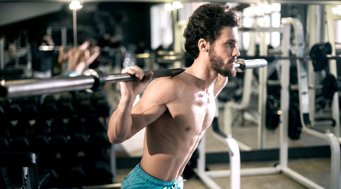 Skinny man working out his upper body with a squat exercise