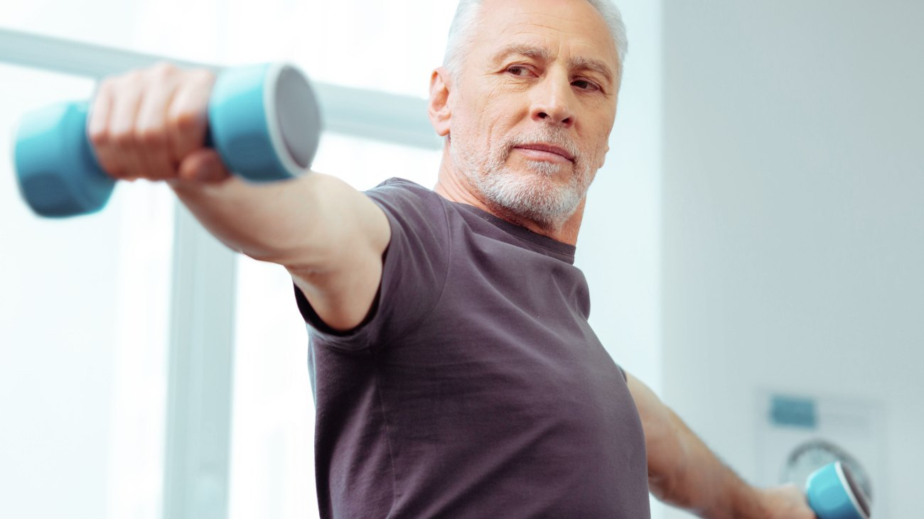 Aging man doing bicep exercises to reverse physical decline