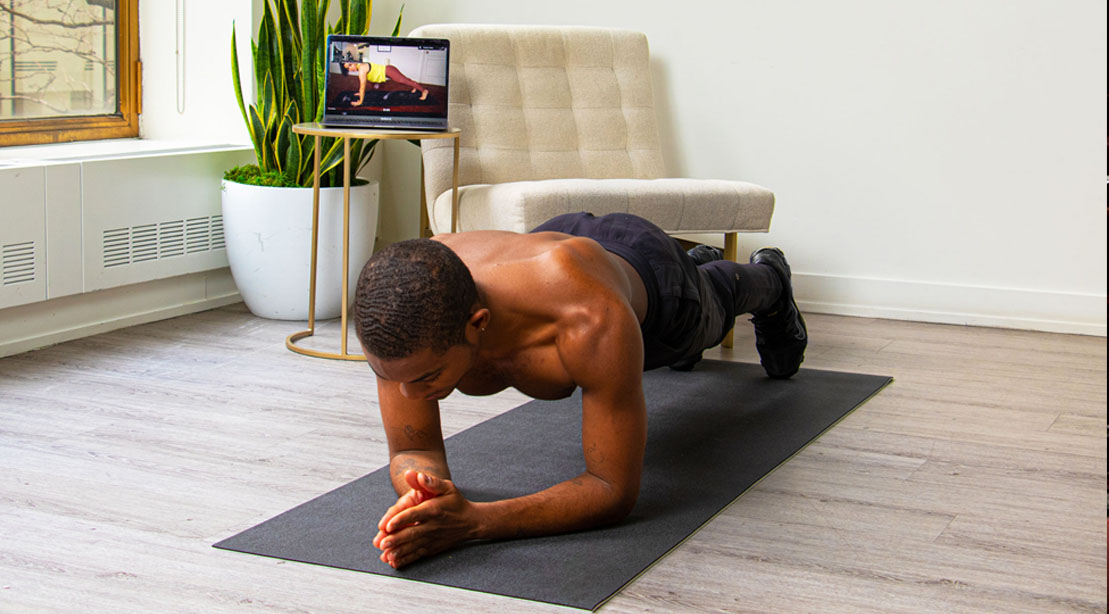Black man planking in his living room and doing at-home workouts using the Flexit app