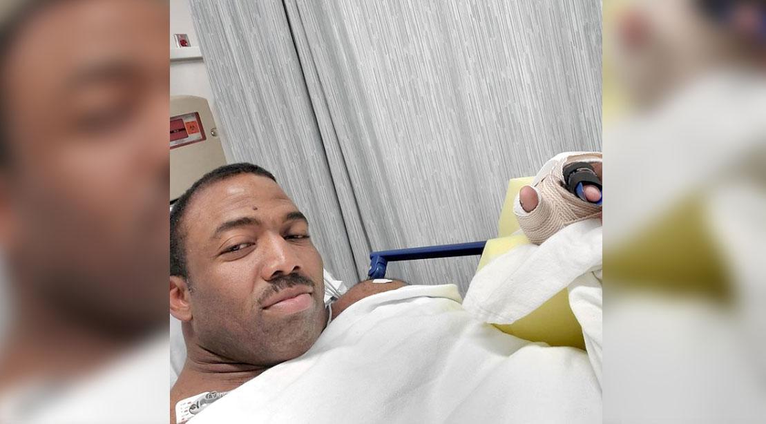 Male bodybuilder Cedric McMillan lying down on a hospital bed after a surgery