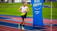 Marathon runner Cj Albertson running on a track next to a Brooks running shoe banner