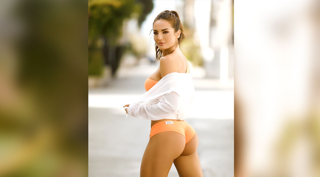 Instagram influencer and fitness guru Whitney Johns showing her glute muscles and butt wearing an orange booty shorts