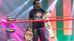 Professional wrestler Rich Swann holding two wrestling championship belts in the wrestling ring