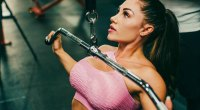 Sexy Instagram fitness influencer and model Caitlin Rice doing an wide lat pulldown
