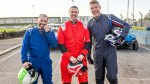Top Gear hosts Chris Harris, Paddy McGuinnes, and Andrew Flintoff standing on a car race track in driving suits