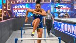 WWE Wrestler Bianca Belair running track hurdles around the wwe wrestling ring