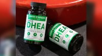 Sheer Strength Labs DHEA bottles next to a weight plate