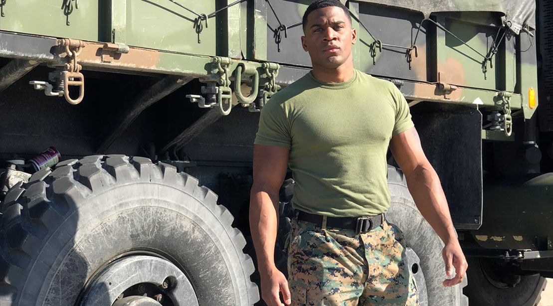 Aaron Marks Wearing Army Fatigues In Front of An Army Truck
