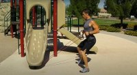Andy McDermott working out in a playground using the fitness tool elastic bands