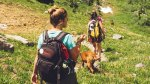 Two female hikers hiking on a hiking trail carrying hiking gear