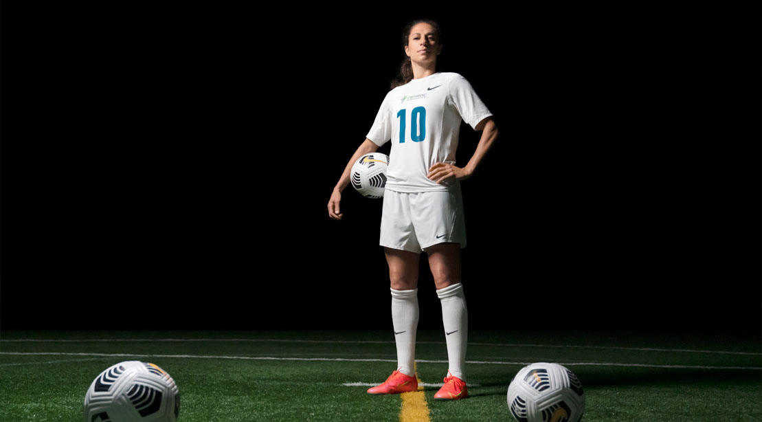 Carli Lloyd holding a soccer ball and standing on a soccer field
