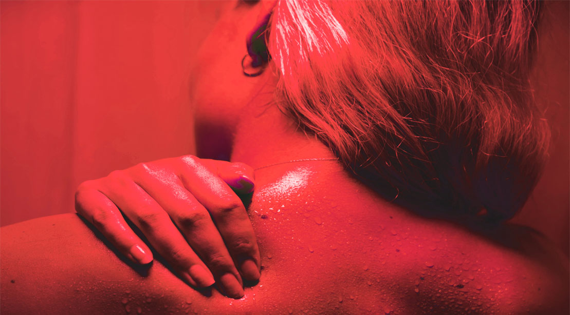 Female using red light therapy to recover from a workout