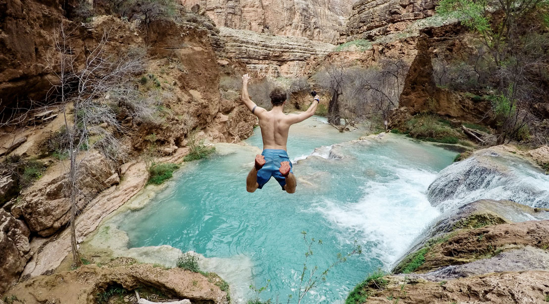 Man jumping down a waterfall as a summer activity