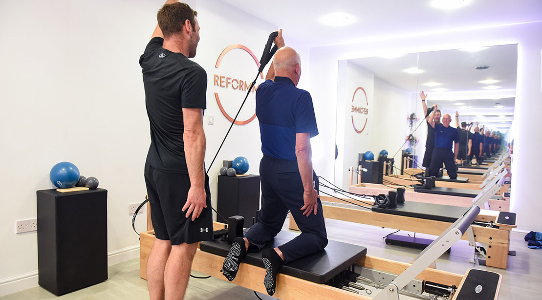 Old man training in pilates with a reformer pilates trainer