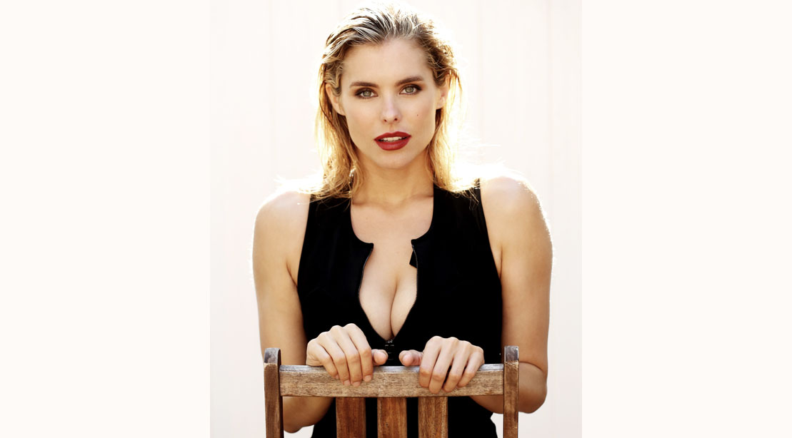 The Forever Purge Star Susie Abromeit sitting on a chair wearing a black shirt