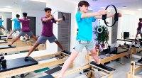 Two boys doing pilates at reformer pilates studio