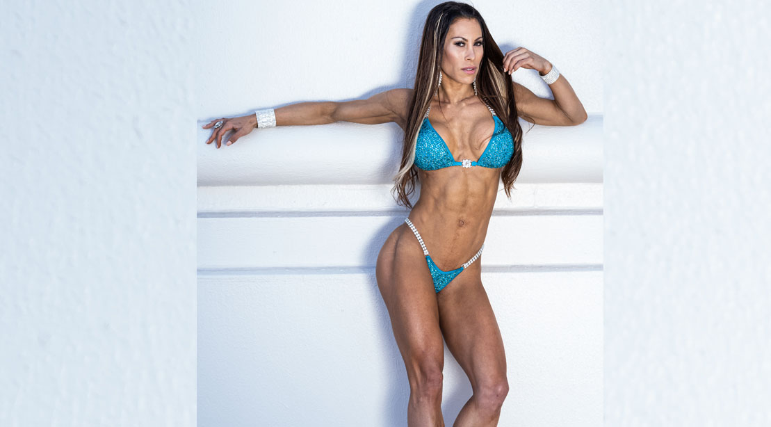 Romina Basualdo posing against a white wall after her shoulder workout routine