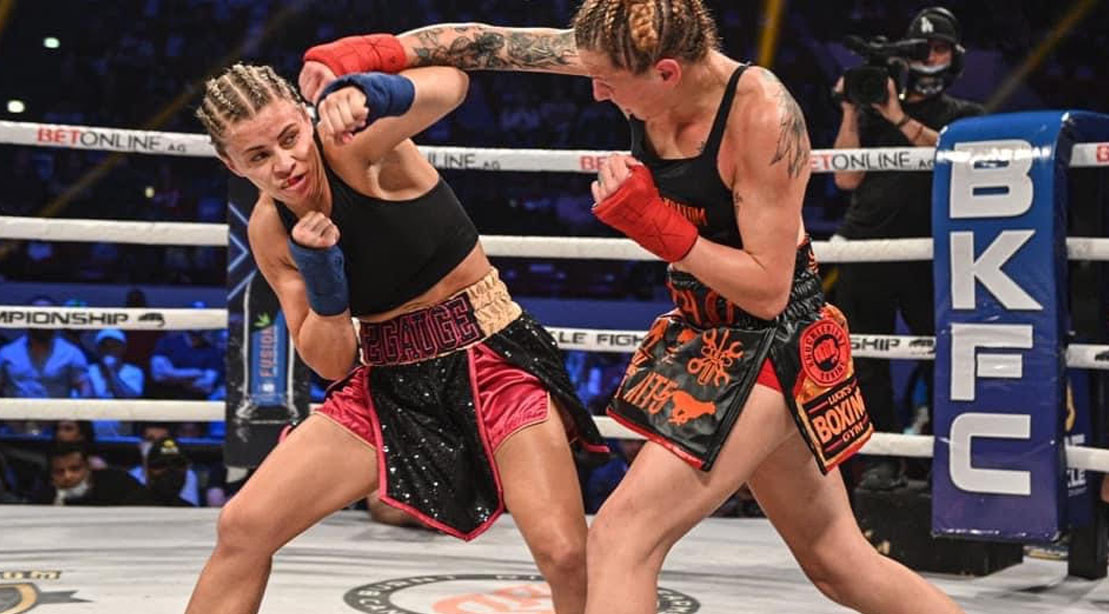 UFC female fighter Paige VanZant blocking a punch in the ring