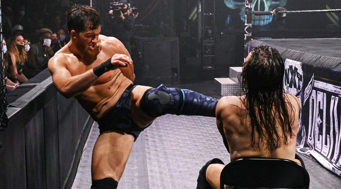 WWE wrestler Kyle O'Reilly kicking another wrestler sitting in a chair