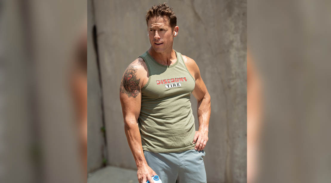 Andy McDermott wearing a muscle shirt and showing off his muscular arms at age 45