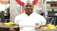 Celebrity chef Andre Chef serving two plates of healthy food to the USO