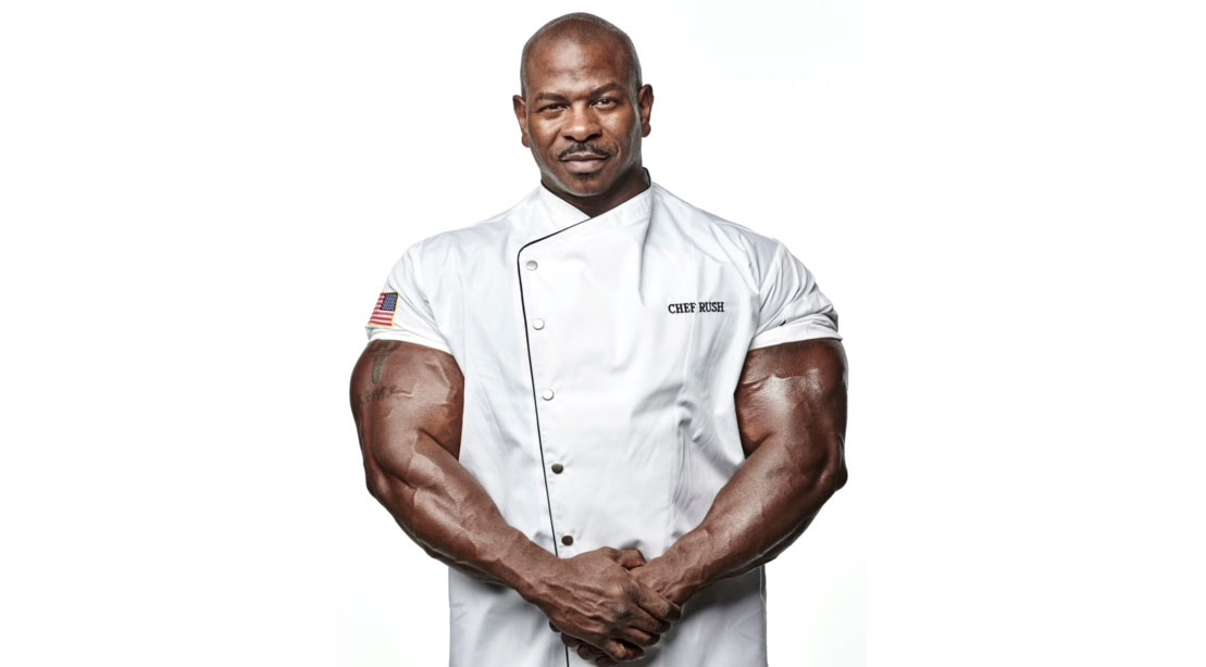 Chef Andre Rush showing off his massive arms while wearing a chef jacket