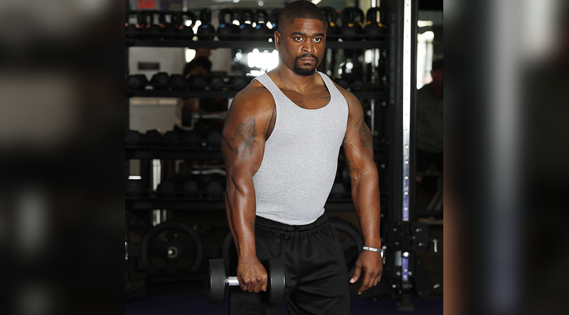 Male performing a X hammer Curl arm exercise for his arm workout