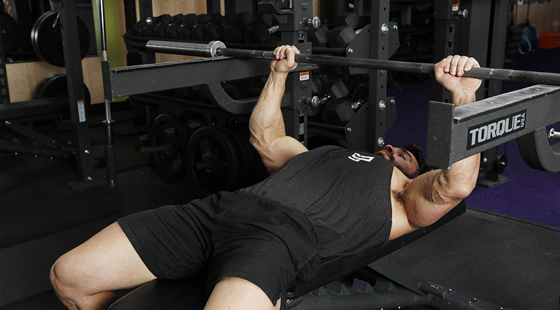 Man performing a high pin press arm exercise for his arm workout