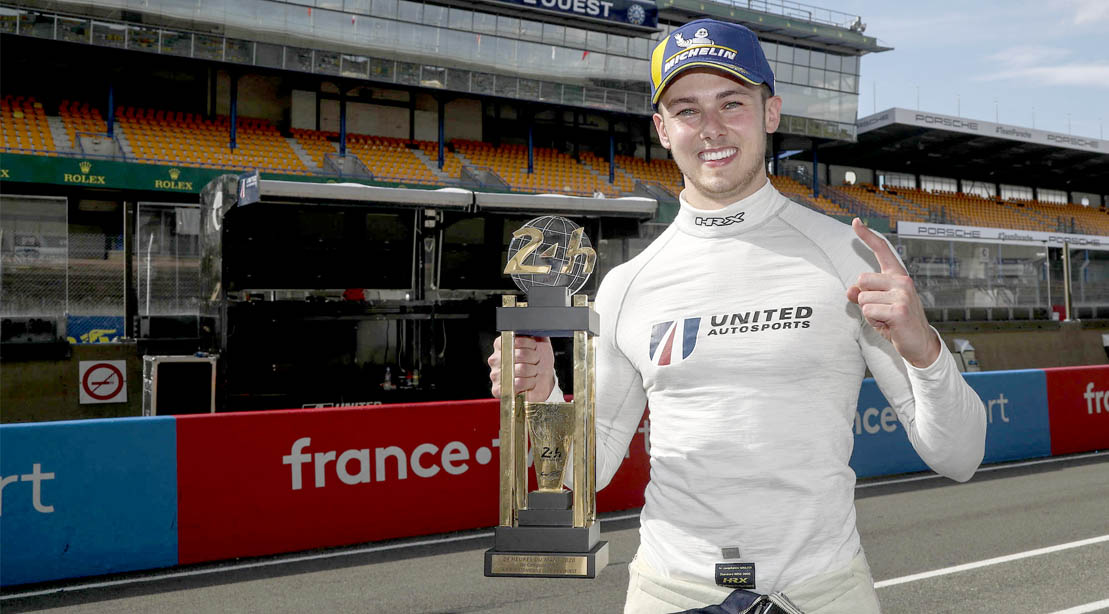 Race car driver Phil Hanson holding the Le Man trophy after winning the Le Mans race