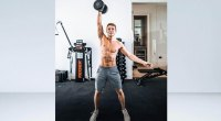Race car driver Phil Hanson performing a compound movement performing a single arm overhead dumbbell press exercise