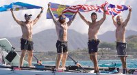 Rowmates Jason Caldwell, Angus Collins, Jordan Shuttleworth, Duncan Roy preparing for the Great Pacific Race holding their country flags and celebrating on a boat in Hawaii